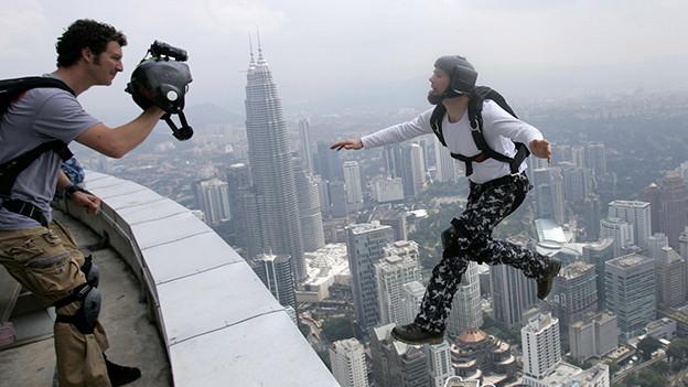 Auf der Suche nach dem Kick und öffentlicher Aufmerksamkeit: Base-Jumper springt vom 421 Meter hohen Tower in Malaysia.