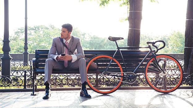 Mann in Anzug auf Bank, daneben ein Fahrrad.