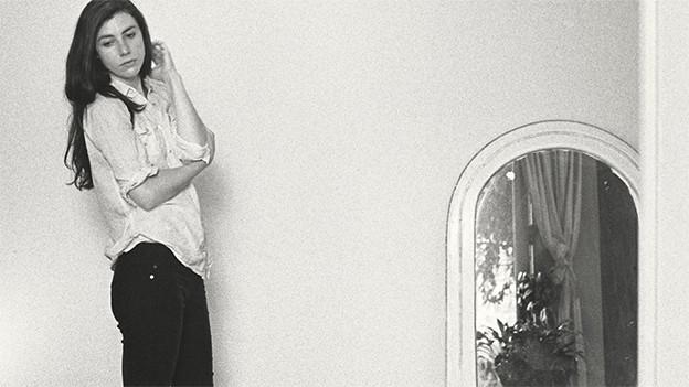 Julia Holter lehnt an der weissen Wand.