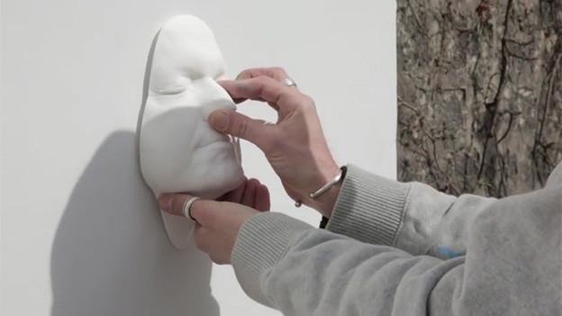 Hand drückt Maske an die Wand.