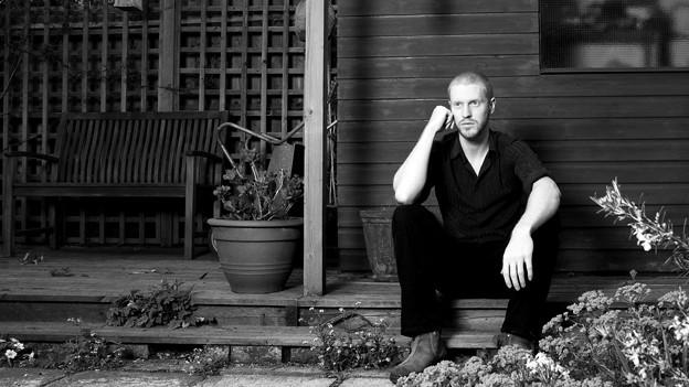 Schwarz-weiss-Foto von Jono McCleery, der vor dem Haus auf einer Treppe sitzt.