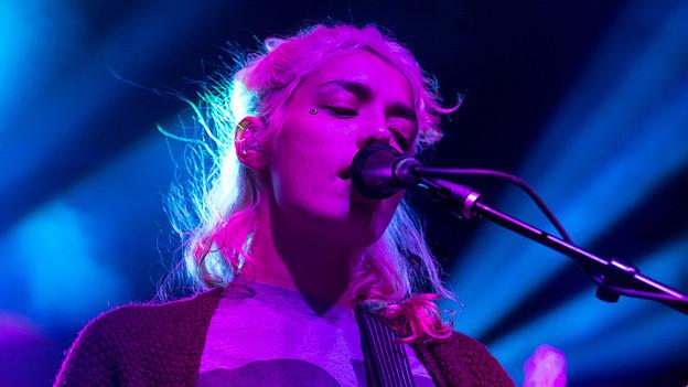 Jennylee singt auf der Bühne im farbigen Scheinwerferlicht.
