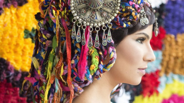 Nahaufnahme einer Frau mit farbigem Kopfschmuck.