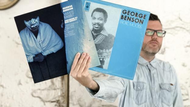 DJ Pesa mit Platten des amerikanischen Jazz-Gitarristen George Benson.