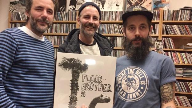 Brachten eine Vinyl-Plakette: Dani (l.) und Reto (m.) bei Andi Rohrer im «Sounds!» Büro.