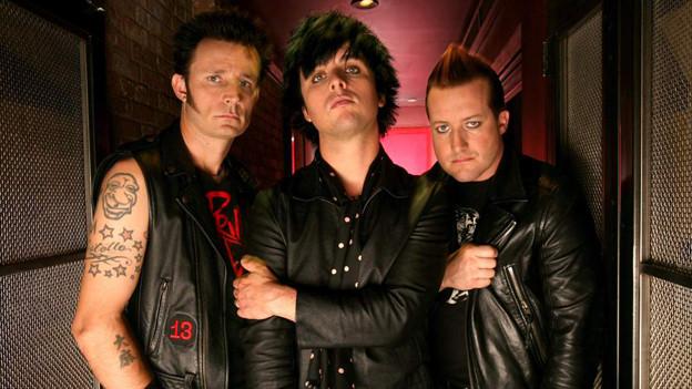 Die Band Green Day posiert für die Kamera.