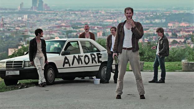 Die Band Wanda vor einem alten Mercedes.