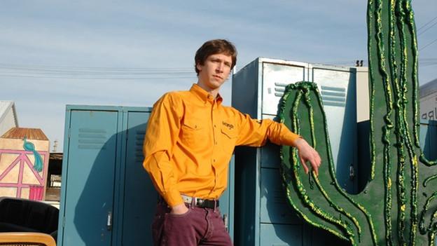 Musiker Jib Kidder lehnt sich an einen Kaktus.