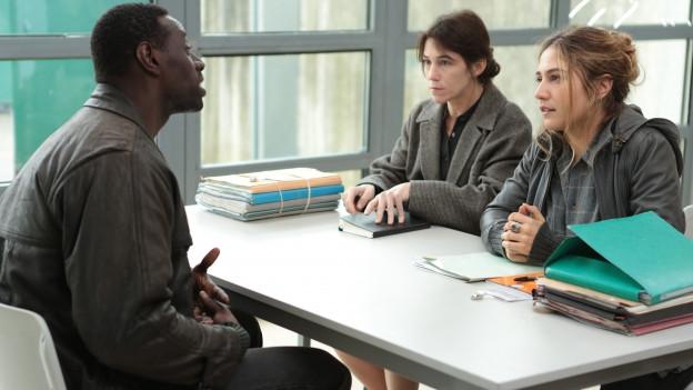 Samba (Omar Sy) spricht mit den Sozialarbeiterinnen Alice (Charlotte Gainsbourg) und Manu (Izia Higelin).