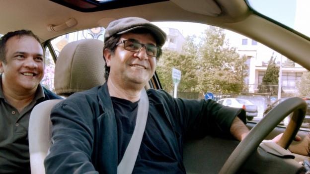 Regisseur Jafar Panahi (rechts) kutschiert den DVD-Verkäufer zu einem Kunden.
