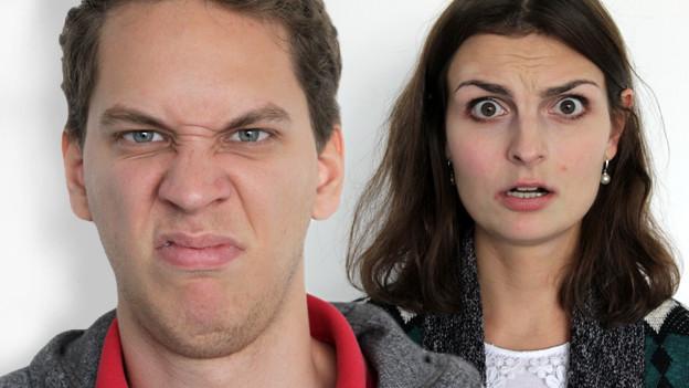 Ein Mann schaut geekelt, eine Frau angstvoll