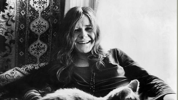 Janis Joplin sitzt, im Vordergrund: Katzen
