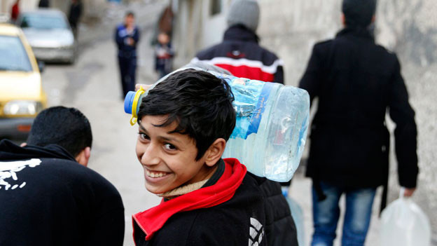 Ein Junge trägt eine Wasserflasche nahe Damaskus