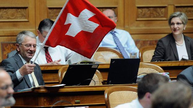Walter Müller (FDP/SG), links, schwenkt eine Schweizerfahne waehrend den Beratungen über das Amtshilfegesuch der USA.