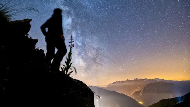 Ein Mann hält Ausschau nach Sternschnuppen auf dem Col du Tronc, oberhalb Verbier.
