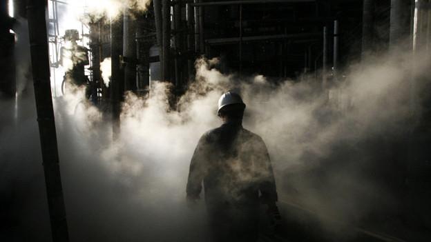 Arbeiter wandert durch eine Öl-Raffinerie