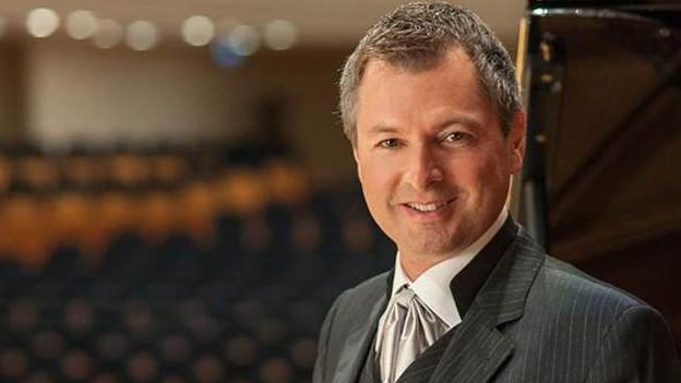 Ein Mann im Anzug in einem Konzertlokal.