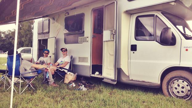 Festival-Besucher vor Wohnmobil.
