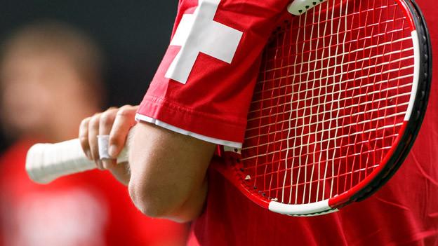 Unter den Arm geklemmtes Tennisracket.