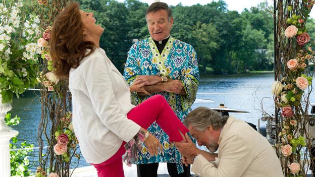 Don Griffin (Robert De Niro) küsst seiner Freundin Bebe (Susan Sarandon) die Füsse, beobachtet von einem sonderbar gekleideten Pfarrer (Robin Williams).