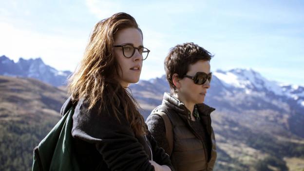 Zu sehen sind die Schauspielerinnen Juliette Binoche und Kristen Steward. Sie stehen in den Bündner Bergen.