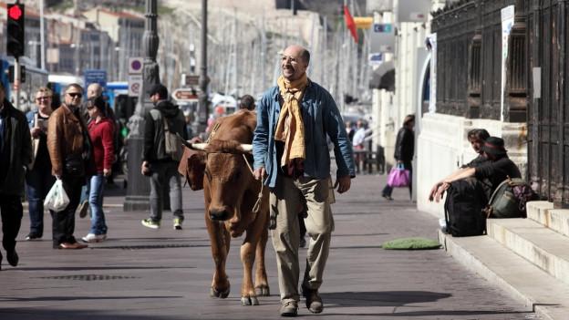 Fatah (Fatsah Bouyahmed) marschiert mit seiner Kuh Jacqueline in Marseille los.