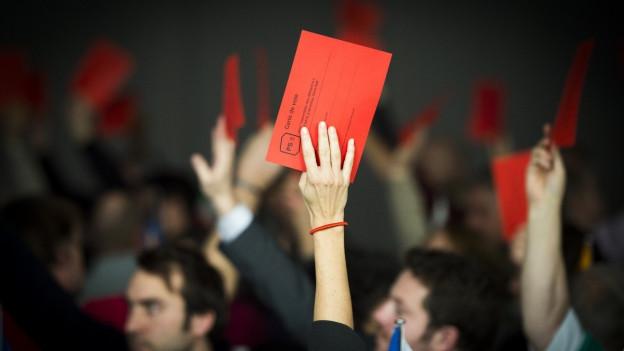 Hände, die rote Abstimmungkarten emporstrecken.