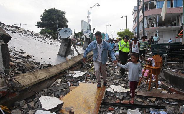 Viele Menschen stehen vor Trümmerhaufen