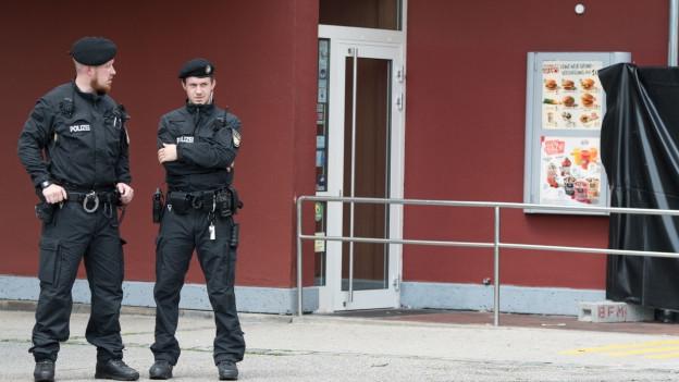 Polizisten am Tag danach vor dem Schnellimbiss.