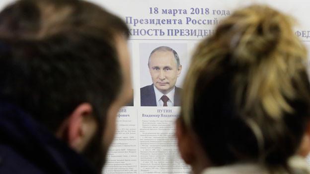 Wähler betrachten ein Bild Putins in einem Wahllokal.