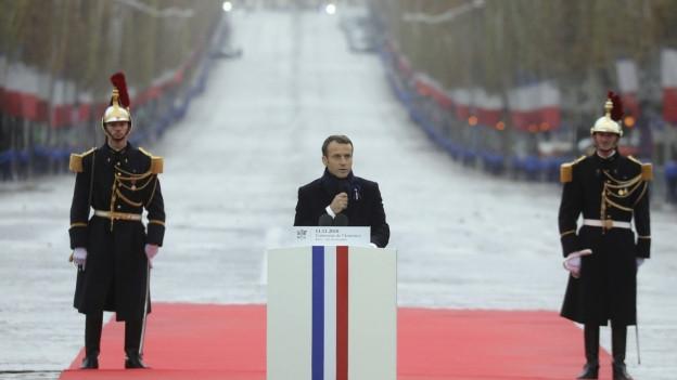 Frankreichs Präsident Emmanuel Macron redet vor dem Triumphbogen in Paris.