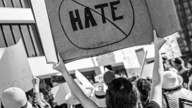 Eine Frau hält ein Schild in die Höhe mit «no hate».