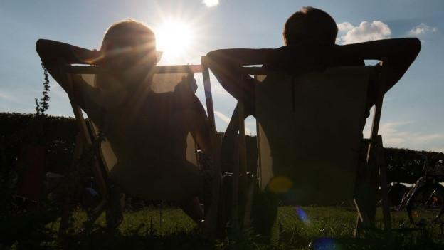 Zwei Menschen entspannen sich im Sonnenschein.