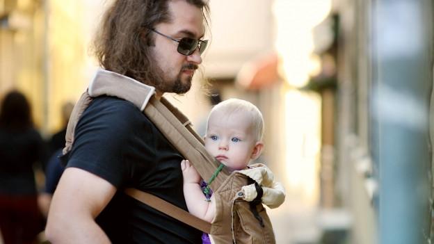 Ein Mann mit langen Haaren und Sonnenbrille trägt sein kleines Kind im Tragetuch.