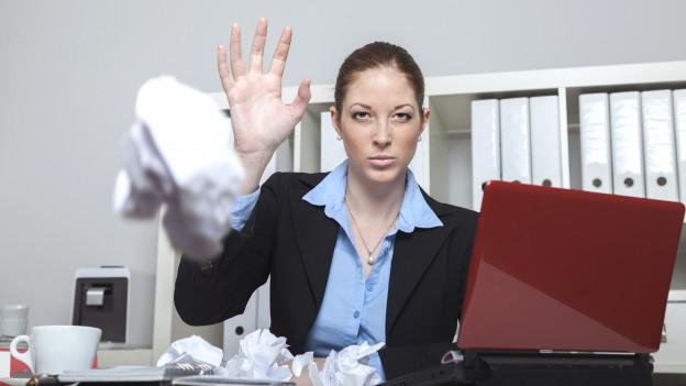 Eine Frau in einem Büro wirft genervt ein zusammengeknülltes Papier Richtung Kamera.