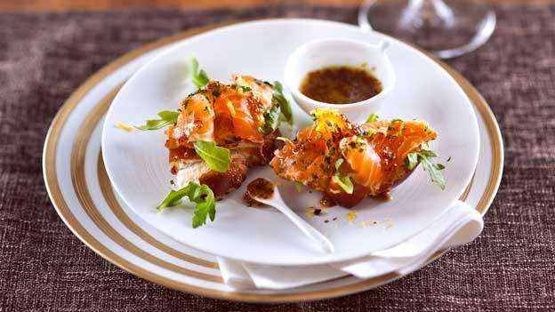 Zu sehen ist opulent drapierter graved Lachs auf einem Teller.