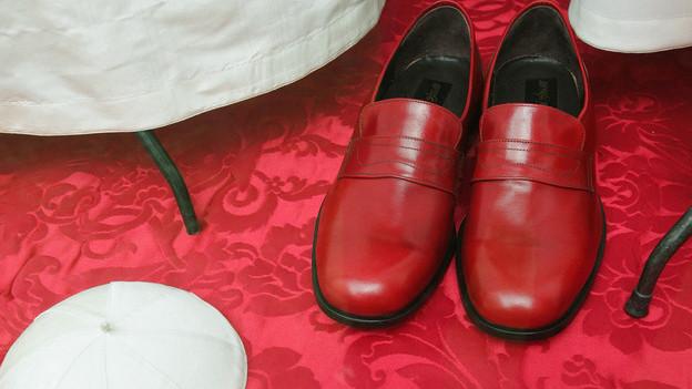 Rote Schuhe darf unter den katholischen Würdeträgern allein der Papst tragen. Der päpstliche Lieferant Gammarelli präsentiert ein burgunderrotes Paar im Schaufenster.