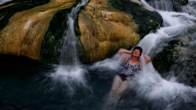 Eine Frau entspannt in einer heissen Quelle in Griechenland.