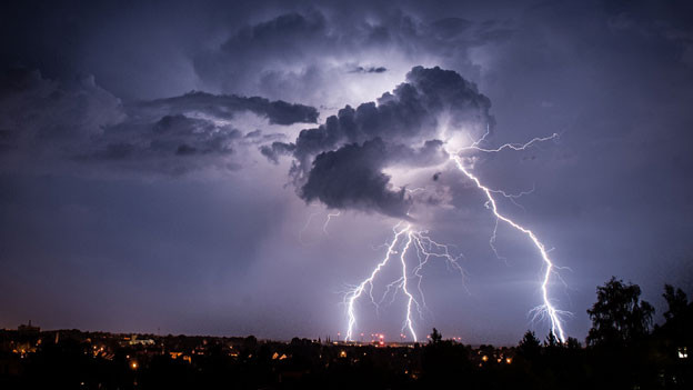 Blitze erhellen den Nachthimmel.