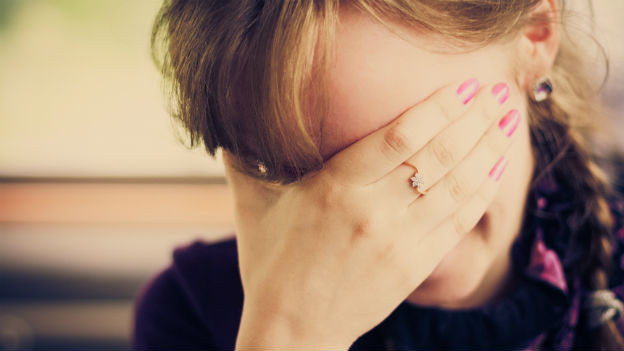 Frau verbirgt das Gesicht in ihren Händen