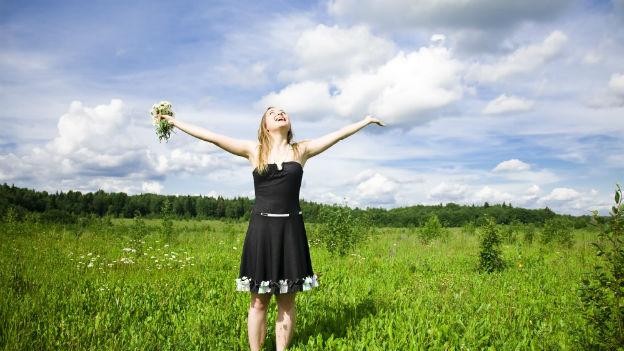 Glückliche Frau mit ausgestreckten Armen in einer Blumenwiese.