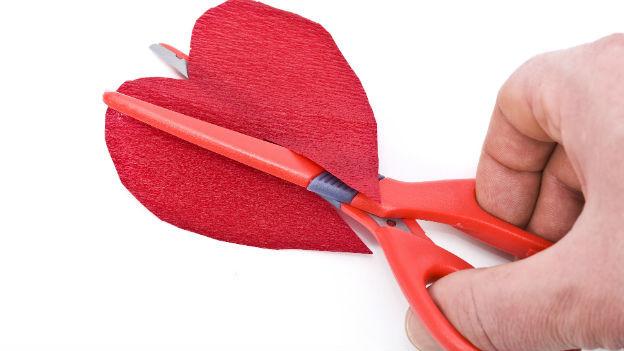Eine Schere zerschneidet ein Herz