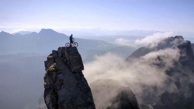 Ein Mann steht mit dem Bike auf einem Berggipfel