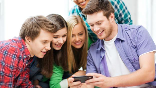 EIne Gruppe junger Menschen schaut in ein Smartphone und amüsiert sich.