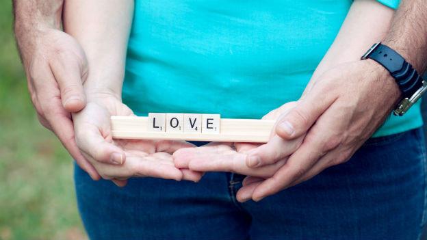 Ein Mann und eine Frau halten Scrabble-Steine: Love