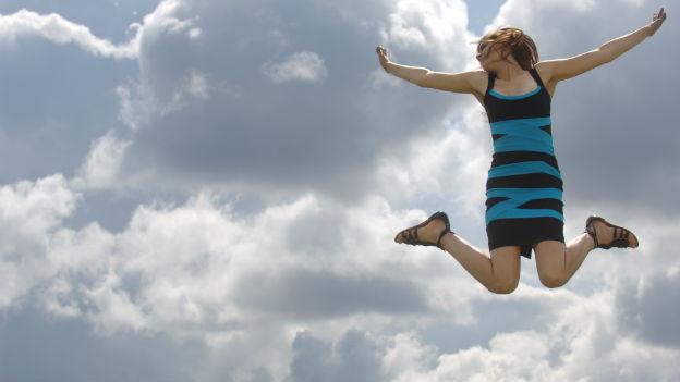 Eine junge Frau springt glücklich in die Luft