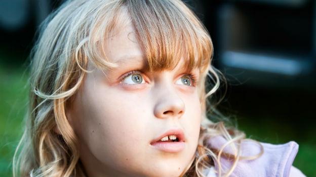 Ein Mädchen schaut verwundert und ungläubig in die Ferne.
