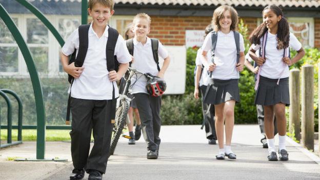 Schüler in Uniform vor Schule