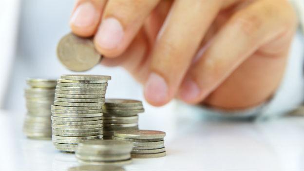 Hand vor einem Stapel Münzen