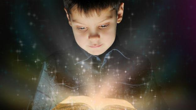 Knabe schaut in ein glitzerndes Märchenbuch